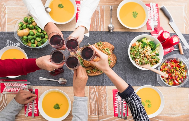 People clanging glasses above festive table Free Photo