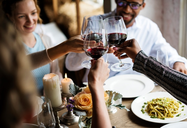People clinging wine glasses together in restaurant Premium Photo