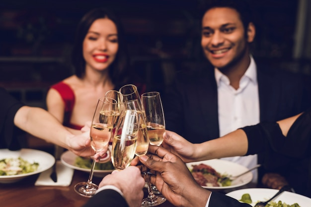 People clink glasses of champagne in a restaurant. Premium Photo