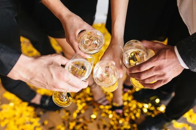 人々はシャンパンでいっぱいのグラスをチリンと鳴らします 無料写真