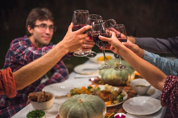 People clinking glasses at table Free Photo