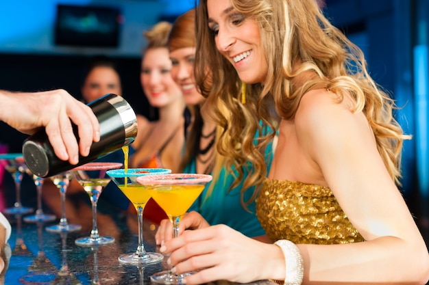 People in club or bar drinking cocktails Premium Photo