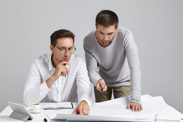 People, collaboration and discussion concept. professional architect coworkers look attentively at blueprint Free Photo