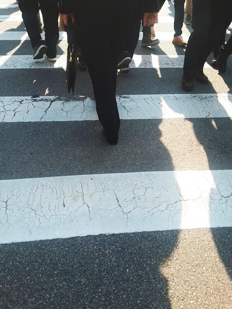 People crossing the street by crosswalk Free Photo