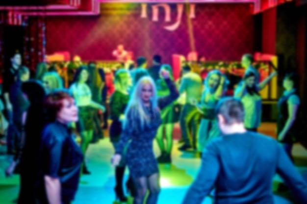 사람들은 나이트 클럽의 댄스 플로어에서 춤을 춥니 다. 밝은 스트로브 조명 프리미엄 사진