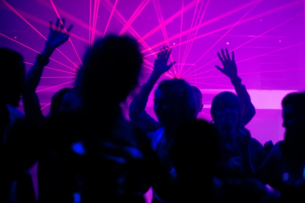 People dancing in club with laser Premium Photo