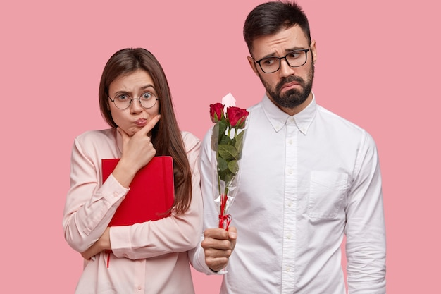 People, dating and relationship concept. displeased bearded man in white elegant shirt gives girlfriend roses, wants to apology Free Photo