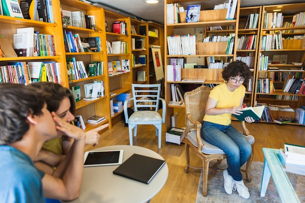 People discussing geeky woman in library Free Photo