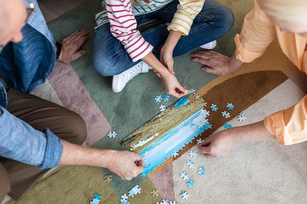 Persone che fanno puzzle sul pavimento da vicino Foto Gratuite