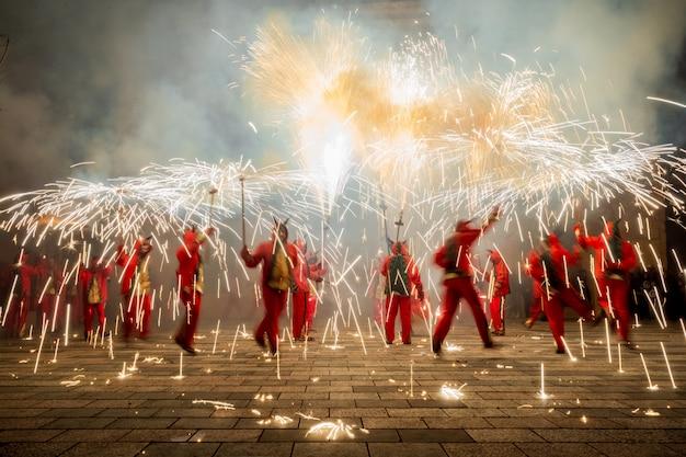 Люди, одетые как демоны, танцуют с фейерверками Premium Фотографии