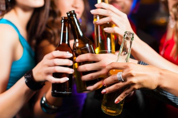 People drinking beer in bar or club Premium Photo