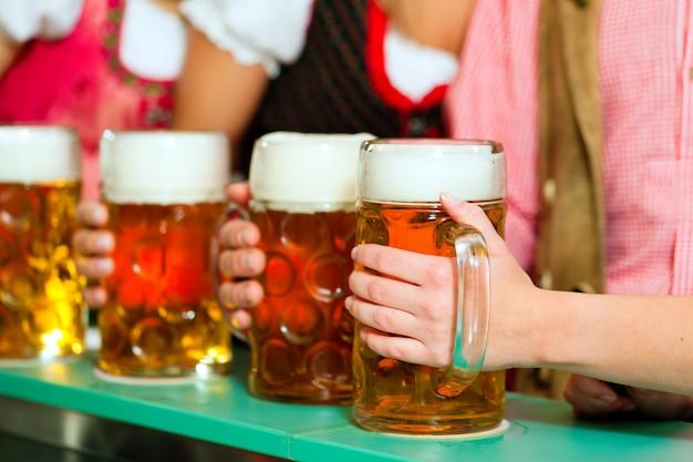 People drinking beer in bavarian pub Premium Photo