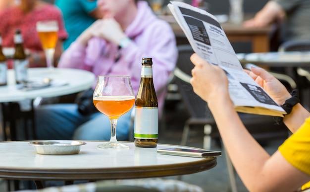 Люди пьют пиво в уличных кафе в старом европейском туристическом городке. Premium Фотографии