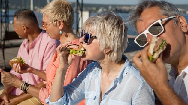 屋外でハンバーガーを一緒に食べる人 無料写真