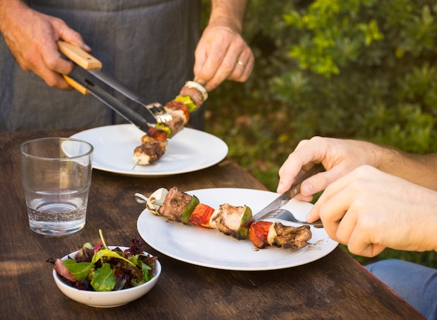 People eating cooked barbecue in plates on table Free Photo