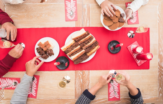 People eating dessert at christmas table Free Photo