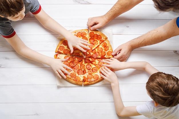 People eating pepperoni pizza. Premium Photo