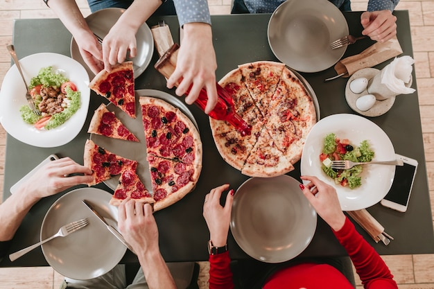 People eating pizza in a restaurant Free Photo