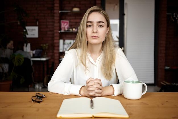 人、教育、仕事、フリーランスのコンセプト。スタイリッシュな若い女性のフリーランサーまたは学生の女の子がカフェのテーブルに座って、コーヒーを飲み、友人やクライアントを待って、彼女の前でコピーブックを開きます 無料写真
