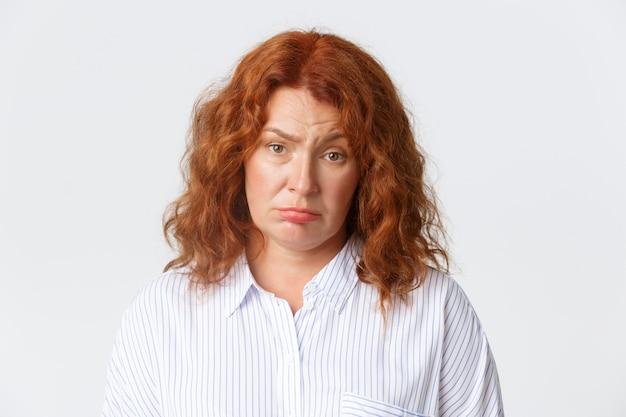 人、感情、ライフスタイルのコンセプト。面白くない疲れた赤毛の中年女性が悲しそうな顔をして、カメラを嫌がり、白い背景の上に暗い立っている。コピースペース 無料写真