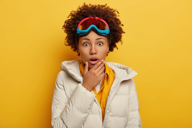 사람, 감정, 취미 및 레저 개념. 겁 먹은 감정적 인 곱슬 아프리카 계 미국인 여자는 푹신한 흰색 코트를 입은 스노우 보드 마스크를 쓰고 턱을 쥐고 있습니다. 무료 사진