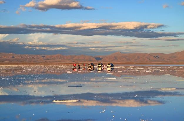 People enjoy the activities on the mirror effect of salar de uyuni salt flats, bolivia Premium Photo