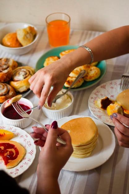 People enjoying breakfast at table Free Photo