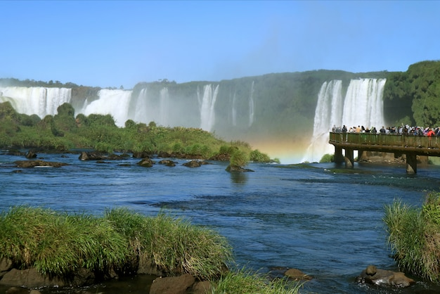 People exploring the powerful iguazu falls with a gorgeous rainbow from the boardwalk, brazil Premium Photo