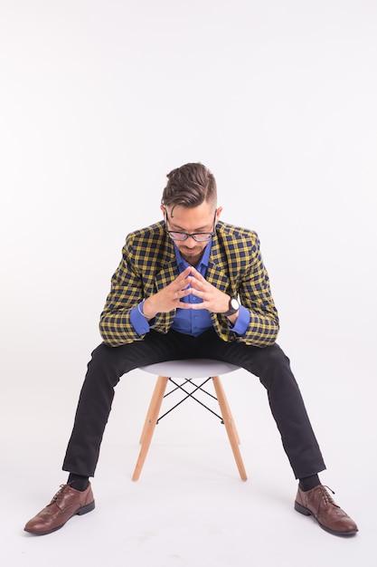 Люди, мода и красота концепции - красивый молодой уверенный в себе мужчина сидит на стуле, изолированном на белой стене Premium Фотографии