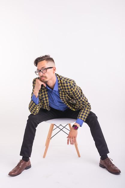 Люди, мода и красота концепции - красивый молодой человек, сидящий на стуле, изолированный на белом Premium Фотографии