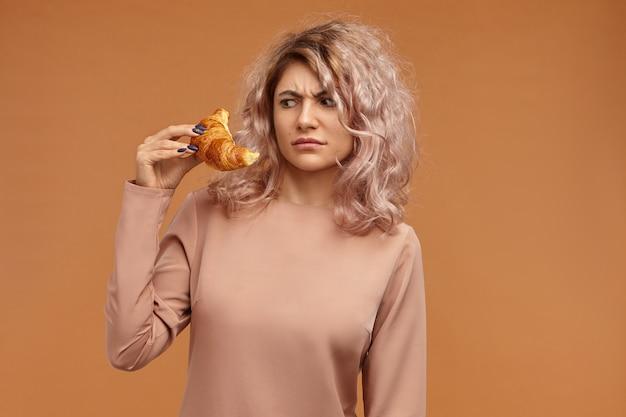 Persone, cibo, pasticceria, prodotti da forno dolci e concetto di dieta. colpo di accigliata frustrata giovane femmina europea con i capelli rosati fissando il croissant in mano Foto Gratuite