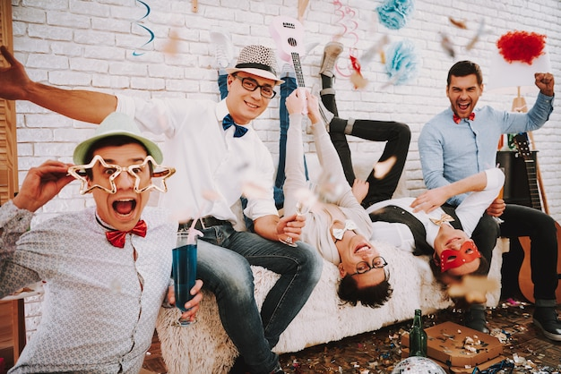 People gay in bow ties playfully posing on couch at party Premium Photo
