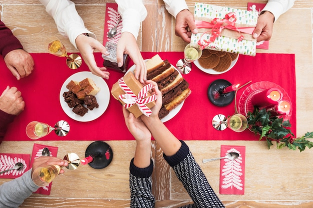 People giving christmas gift boxes to each other at festive table Free Photo