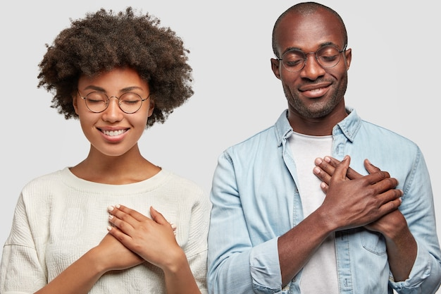 People and gratitude concept. horizontal shot of pretty young african american female and dark skinned male keep hands on chest, being thankful to people who helped them, have charming smiles Free Photo