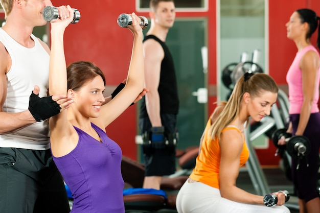 People in gym exercising with weights Premium Photo