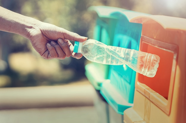 People hand holding garbage bottle plastic putting into recycle bin for cleaning Premium Photo