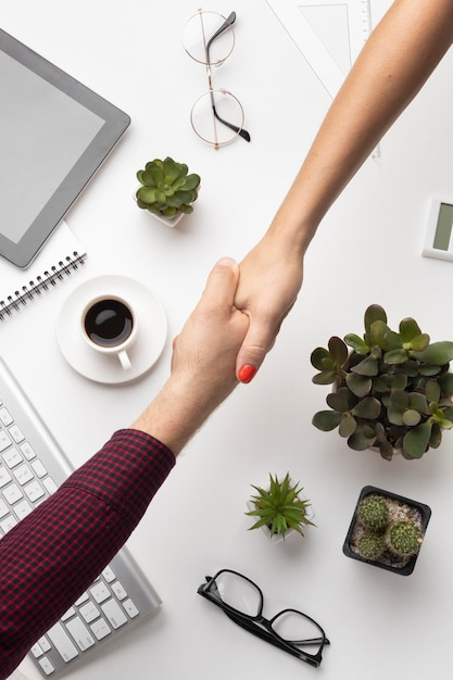 People hand shaking above an office desk Premium Photo
