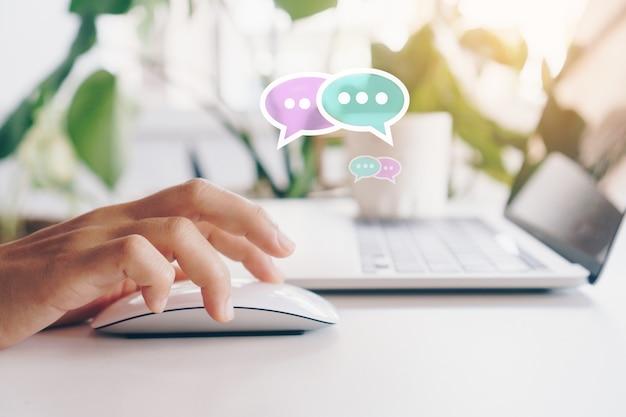 채팅 아이콘 팝업에서 노트북 입력, 채팅 또는 문자 메시지를 사용하는 사람들의 손. 기술 개념을 만드는 소셜 미디어. 빈티지 부드러운 색조 배경입니다. 프리미엄 사진