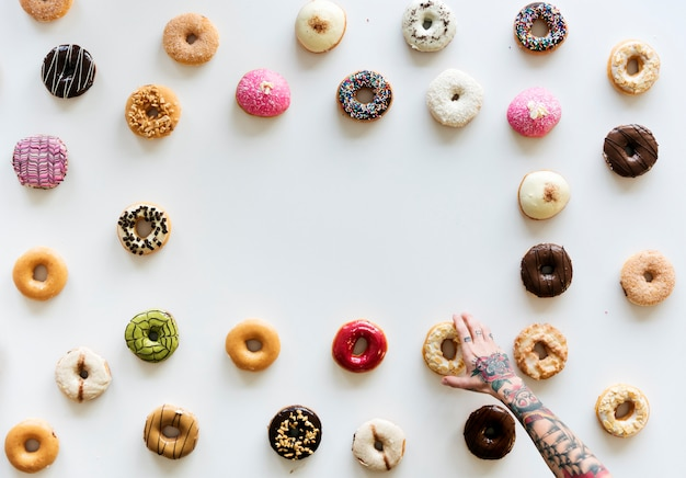 People hands reach for doughnuts Premium Photo