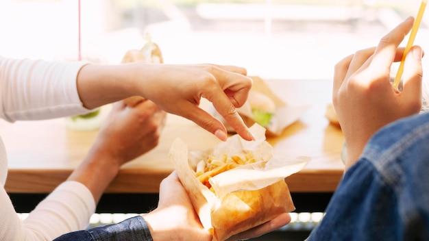 Люди, которые едят фаст-фуд с картофелем фри Бесплатные Фотографии