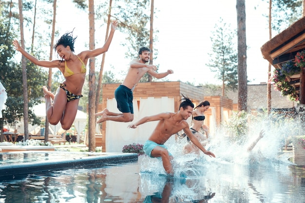 People having fun by jumping from poolside into water Premium Photo