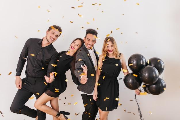 Persone che si divertono alla festa con palloncini neri e coriandoli Foto Gratuite