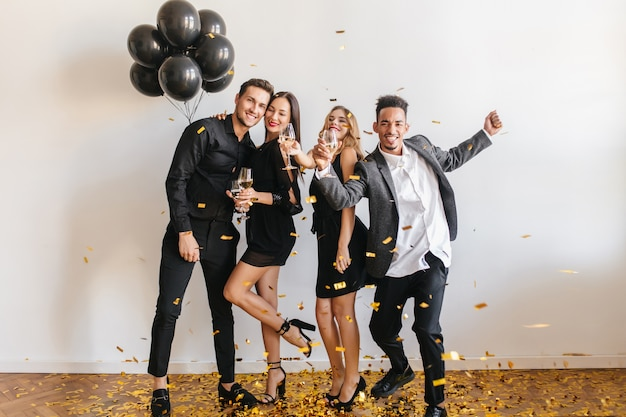 People having fun at the party with black balloons and confetti Free Photo
