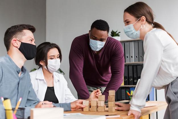 Persone che hanno una riunione in ufficio durante una pandemia con le maschere Foto Gratuite
