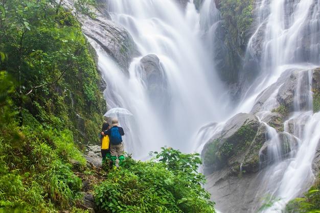 Люди в походе возле водопада Premium Фотографии