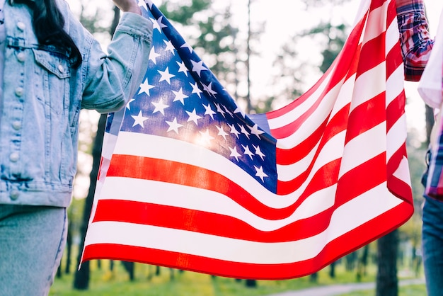 People holding flag of usa in park Free Photo
