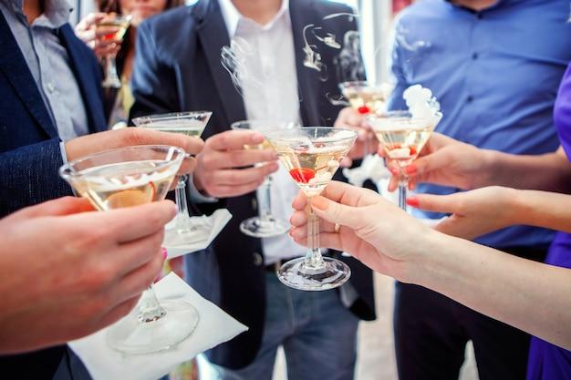 乾杯するシャンパングラスを持っている人、グラスを持った手 Premium写真
