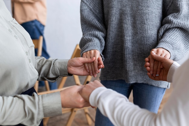 People holding hands at a group therapy session Premium Photo