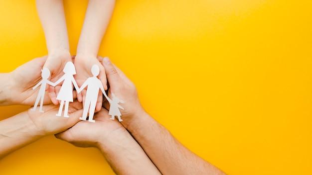 Люди держат бумажную семью в руках на желтом фоне Premium Фотографии
