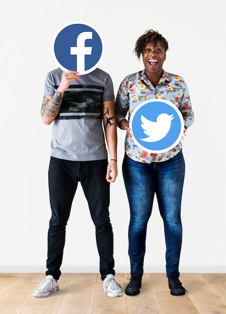 People holding two social media icons Free Photo
